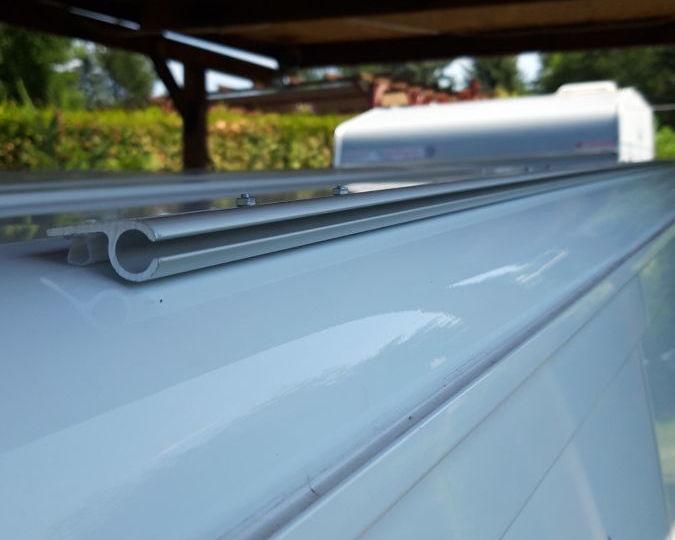 Binario tubolare per il fissaggio della tenda da sole al trasportatore